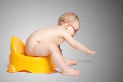 戴眼镜的小婴孩坐洗手间 库存照片