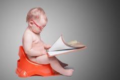 戴眼镜的小婴孩坐洗手间 免版税图库摄影
