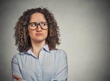 戴眼镜的生气的可疑少妇 免版税库存图片