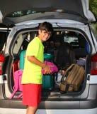 戴眼镜的男孩在汽车的后车箱装载了行李 免版税库存照片