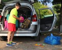 戴眼镜的男孩在汽车的后车箱装载了行李 免版税库存图片