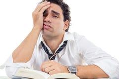 戴眼镜的疲乏的人在坐与书的白色衬衣 库存图片