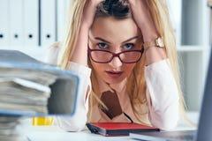 眼镜的疲倦的和被用尽的妇女看照相机在扶植她的头的文件附近山用她 免版税库存照片