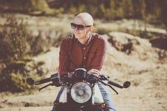 戴眼镜的秃头人坐一辆老葡萄酒摩托车 库存图片
