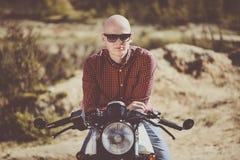 戴眼镜的秃头人坐一辆老葡萄酒风俗自行车 库存图片
