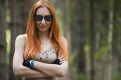 戴眼镜的红发女孩倾斜了反对树 库存图片