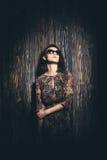 戴眼镜的美丽的女孩在木背景 库存照片