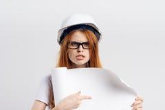 戴眼镜的美丽的妇女工程师在白色背景拿着一张图画,工程学,建筑,画象 图库摄影
