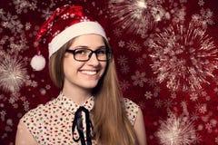 戴眼镜的美丽的微笑的女孩在看的圣诞老人帽子 库存图片