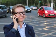 戴眼镜的美丽的成熟女实业家使用在繁忙的城市街道上的手机 免版税库存照片