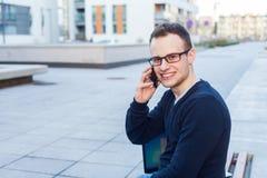戴眼镜的英俊的年轻学生使用手机。 库存照片