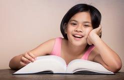 戴眼镜的获得的女孩读和乐趣。 免版税图库摄影