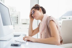 戴眼镜的被聚焦的女实业家使用计算机 免版税库存照片
