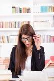 戴眼镜的迷茫的女学生 免版税图库摄影