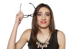 戴眼镜的迷茫的妇女 免版税库存照片