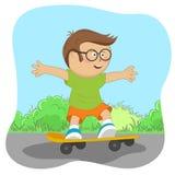 戴眼镜的逗人喜爱的矮小的书呆子男孩在路的滑板 库存图片