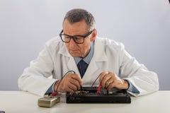 戴眼镜的高级技术员,修理计算机 图库摄影