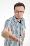戴眼镜的年轻人给手震动 免版税库存照片