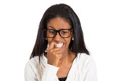 戴眼镜的紧张的妇女咬住她的指甲盖的 库存照片