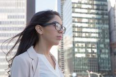 戴眼镜的年轻拉丁职业妇女在城市 免版税库存图片