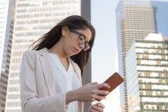 戴眼镜的年轻拉丁职业妇女在城市 图库摄影