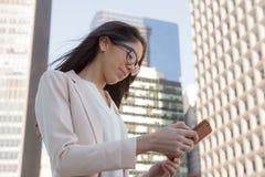 戴眼镜的年轻拉丁职业妇女在城市 免版税库存照片