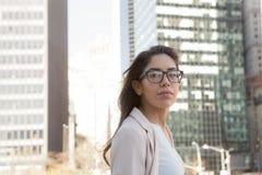 戴眼镜的年轻拉丁职业妇女在城市 库存照片