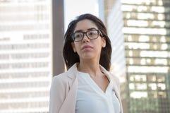 戴眼镜的年轻拉丁职业妇女在城市 库存图片