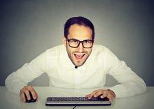 戴眼镜的年轻疯狂的看的商人键入在键盘的 免版税库存图片