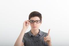 戴眼镜的滑稽的严密的老师震动他的在白色背景的手指 免版税库存照片