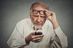 戴眼镜的年长人有麻烦看见手机的 免版税库存图片