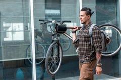 戴眼镜的年轻骑自行车者人运载在他的肩膀Liаestyle每日定期概念的自行车 库存照片