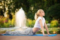 眼镜蛇姿势的瑜伽妇女 免版税库存图片