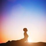眼镜蛇瑜伽姿势的妇女思考在日落的 禅宗 库存照片