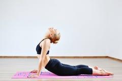 眼镜蛇瑜伽姿势的妇女 免版税库存照片