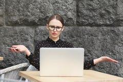 戴眼镜,在调查膝上型计算机的咖啡馆的黑衬衣的惊奇的妇女 免版税库存图片