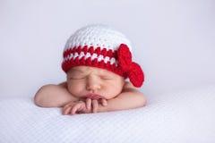 戴着一个白色和红色钩针编织的帽子的新出生的女婴 免版税图库摄影