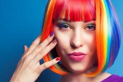 戴着五颜六色的假发和显示五颜六色的钉子的美丽的妇女 免版税库存图片