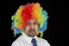 戴着五颜六色的假发的商人看起来不耐烦 库存照片
