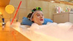 戴着化妆面罩的美丽的深色的妇女在泡沫似的浴放松 秀丽治疗在家 免版税库存照片