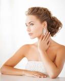 戴着发光的金刚石耳环的妇女 免版税库存图片