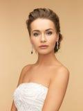 戴着发光的金刚石耳环的妇女 免版税库存照片