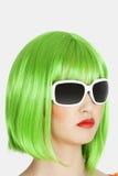 戴着在灰色背景的少妇绿色假发 免版税库存照片