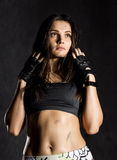 戴着在黑暗的背景的强的性感的女性拳击手或Muttahida Majlis-E-Amal战斗机黑手套 库存照片