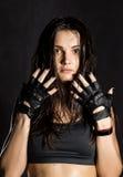 戴着在黑暗的背景的美丽的性感的女性拳击手或Muttahida Majlis-E-Amal战斗机黑手套 免版税库存照片