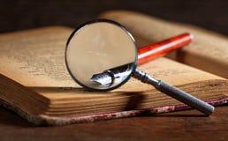 着墨笔和放大镜在一本旧书 免版税库存图片