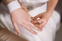 戴着她的新郎的新娘一个婚戒 库存图片