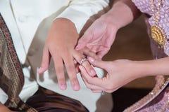 戴着她的新郎的新娘一个婚戒 免版税库存照片