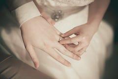 戴着她的新郎的新娘一个婚戒 免版税图库摄影