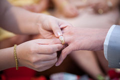 戴着她的新郎的泰国新娘一个婚戒 免版税库存图片